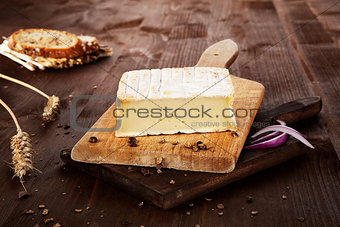 Cheese on wooden board. Agricultural background.