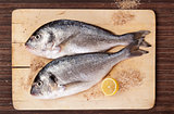 Two fish on wooding kitchen board.