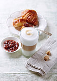 Glass of Latte Macchiato and Croissant with Rhubarb Jam
