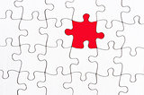 blank white jigsaw with one red piece