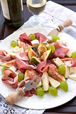 Appetizer with prosciutto, figs, cheese and grapes