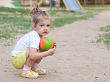 Little girl sitting on his haunches with a ball Playground