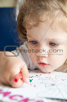 Girl draws a pencil on sheet of paper