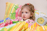 Two-year-old girl is in bed under the blanket