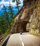 Biker riding into mountainous tunnel