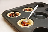Spooning mincemeat into pastry cases