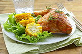 baked chicken leg with corn for garnish