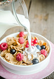 Milk pouring into plate with granola and fresh berries