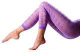 Female legs in purple leggings over white background