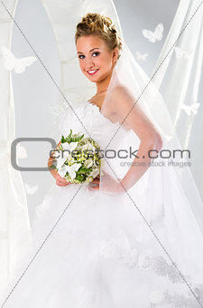 Beautiful bride with bouquet of flowers over summer background
