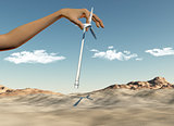 Hand placing wind turbines in a desert