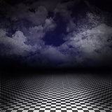 Empty, dark image with black and white checker floor on the ground and ray of light in cloudy, dark blue sky