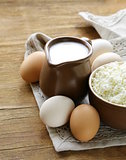 rustic products cottage cheese, milk and eggs on a wooden table