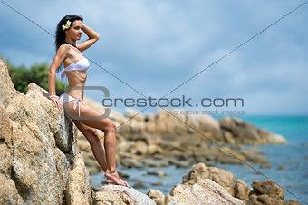 Beautiful young woman relaxing on a rock