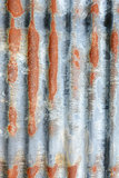 Vertical corrugated iron sheet with patches of rust