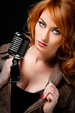 Beautiful redhead woman with retro microphone