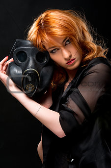 Redhead woman holding gas mask