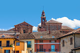 Church's bell tower and colorful houses in La Morra.