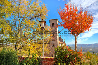 Old belfry among autumnal trees in Piedmont, Italy.
