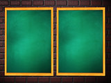 Two chalkboards of green color on brick wall