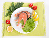 Raw salmon steak red fish on a plate decorated with vegetables
