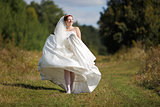 Happy caucasian bride walking field.