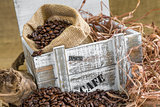 scattered roasted coffee beans in front of old wooden box with a