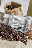 scattered coffee beans around wooden box with a burlap bag