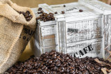 wooden box from the supply of coffee next to burlap bag filled w
