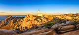 Rocky ocean coastline panorama with lighthouse at sunset