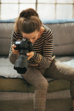 Young woman using modern dslr photo camera