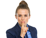 Portrait of business woman showing shh gesture