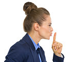 Profile portrait of business woman showing shh gesture