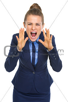 Angry business woman shouting through megaphone shaped hands