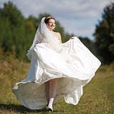 Happy caucasian bride walking field.