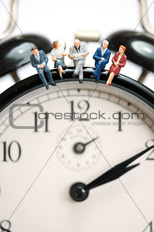 Business team sitting on top of the giant clock
