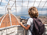 Boy looking through a sightseeing binoculars the Dome of Basilic