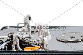 Group of criminologists inspecting broken hard rive