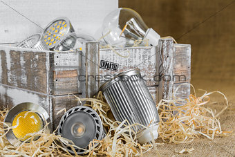 GU10 LED bulbs on straw in front of old delivery wooden box with