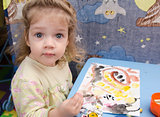 Two-year-old girl is painting at table and looks