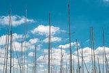 Ship masts over blue sky background