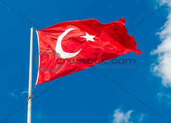 Waving flag of Turkey over blue sky background