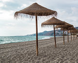 Straw parasols on empty beach. Nerja, Spain
