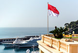National flag of of the Principality of Monaco and view of port
