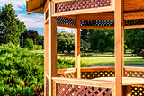 Outdoor wooden gazebo over summer landscape background