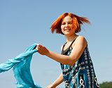 Portrait of a beautiful young woman outside running on the beach with a scarf