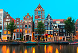 Night city view of Amsterdam canals and typical houses, Holland,