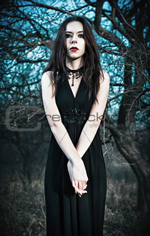 Sad gothic girl stands among autumnal trees