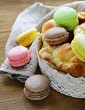 traditional French pastries croissants and macaroons in a lace basket