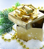 golden gift box with beautiful ribbon in the snow, christmas still life
